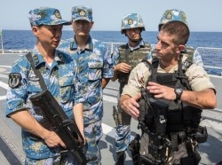 A U.S. gunnery officer discusses techniques with Chinese sailors before a joint counter-piracy exercise in the Gulf of Aden, August 24, 2013