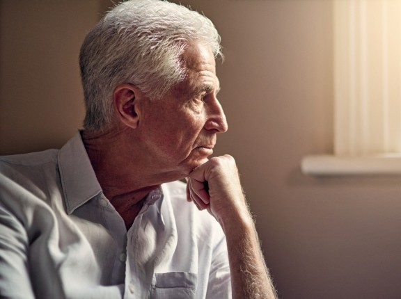 Elderly man with chin on his fist, looking out a sunny window