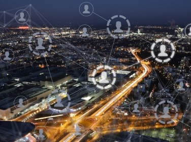 Social network illustration superimposed over a city at night