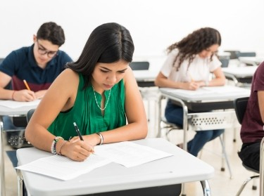 Confident student writing exam in classroom at high school, photo by AntonioDiaz/AdobeStock