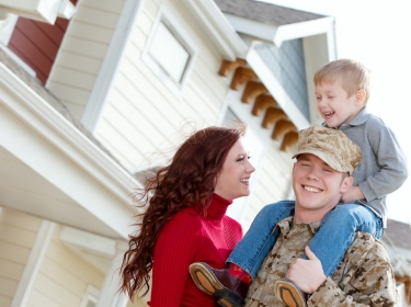 A U.S. Marine Corps soldier and his family outside their home, photo by DanielBendjy/Getty Images