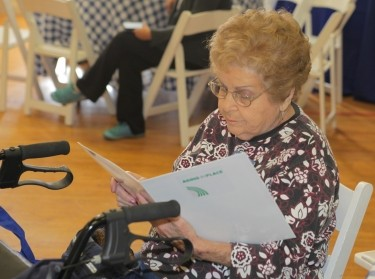 An attendee at a community meeting reads materials about aging in place in West Hollywood, California, May 9, 2015