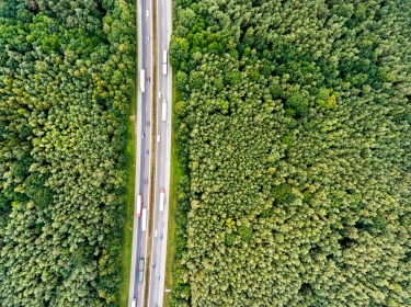 Aerial view of a highway with cars and trucks in the middle of a green forest
