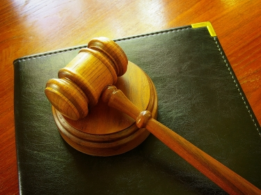 Legal gavel and leather binder on a desk