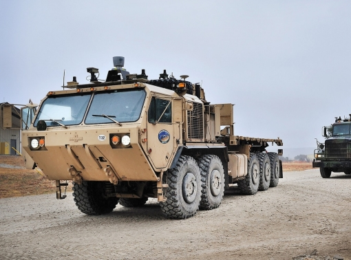 An M1075 palletized load system truck and an M915 line-haul tractor are equipped with add-on kits that transform the vehicles to be fully autonomous, photo by Bruce Huffman/U.S. Army