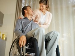 a man sitting in a wheelchair with his partner or wife at his shoulder