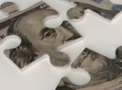 One hundred dollar bill puzzle pieces, photo by gazanfer/Getty Images
