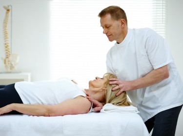 Chiropractor adjusting the neck of a female patient