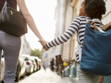 Seen from behind, a woman holding hands with her daughter on a city sidewalk