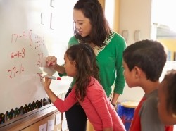 Math teacher and elementary students writing on a whiteboard