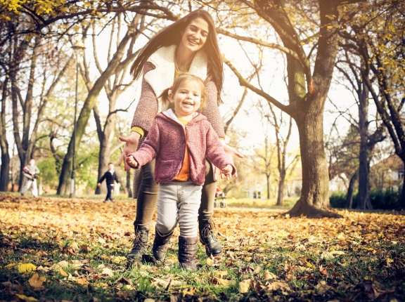 A young mother and her daughter walk through a park