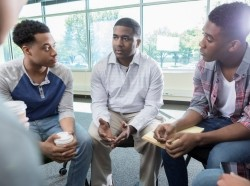 African American men seated in a circle having a discussion