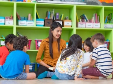Asian female teacher teaching diverse group of kids reading book sitting on library floor in classroom