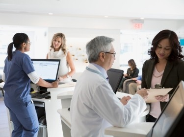 Receptionist and doctor talking to patients in a busy waiting room