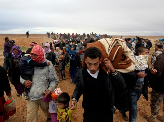 Syrian refugees cross into Jordanian territory, near the town of Ruwaished, 149 miles east of Amman, December 5, 2013, photo by Muhammad Hamed/Reuters
