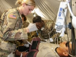 Capt. Tara Brouse, critical care nurse, intensive care unit, Madigan Army Medical Center, assists with treating a mock patient at the Internal Care Ward of the 131st Field Hospital, 528th Hospital Center, photo by U.S. Army