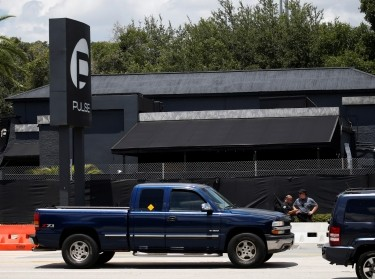 Police officials stand on the sidewalk as cars drive on the road in front of the Pulse night club, following a shooting in Orlando, Florida, June 21, 2016