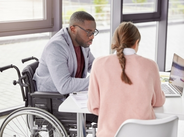 A man in a wheelchair sitting at a desk with a woman looking at a laptop