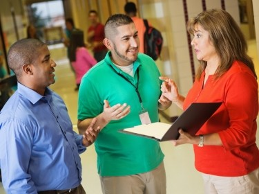 A teacher, coach, and principal talking in a school hallway