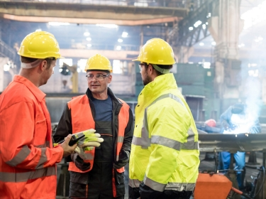 Three male workers wearing personal safety equipment in a factory