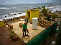 Roberto Figueroa Caballero sits on a small table in his home destroyed by Hurricane Maria, in La Perla neighborhood on the coast of San Juan, Puerto Rico, October 5, 2017, photo by Ramon Espinosa/AP Photos
