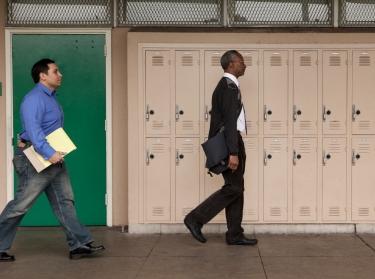 A principal and teacher walking in a school corridor