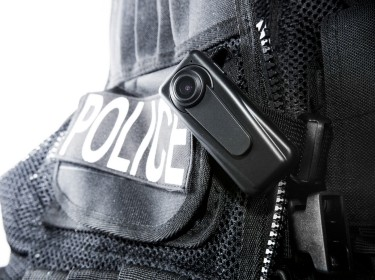 A close-up image of a police body camera clipped to a vest