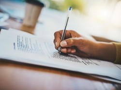 Hand writing on a document, photo by PeopleImages/Getty Images