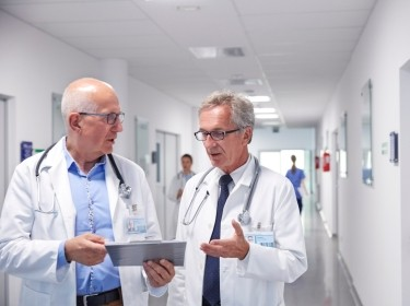 Two male doctors talking in a hospital corridor