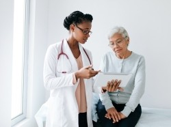 A female doctor standing next to an elderly female patient, pointing to a digital tablet, photo by aldomurillo/Getty Images