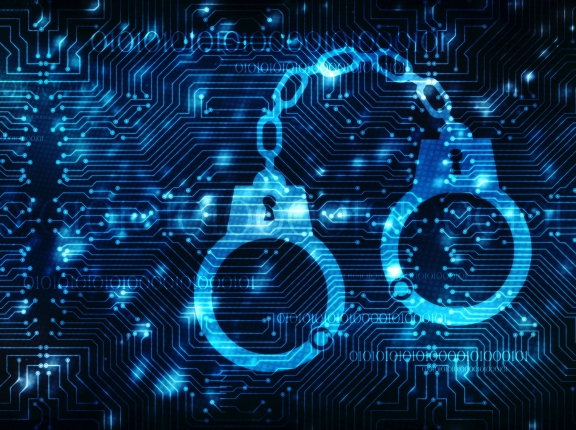 Cybercrime concept of handcuffs icon on a digital background, photo by blackboard/Adobe Stock
