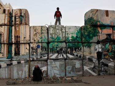 boy watching a graffiti artist in Cairo