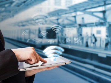 A person holding a tablet with a graphic representing WiFi