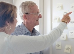 Elderly couple looking at sticky notes on a wall, photo by MonicaNinker/Getty Images