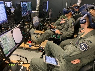 Royal Air Force Flying Officer Syd Janota, Pilot Training Next 2.0 student, observes a fellow student flying a virtual-reality training sortie at the PTN facility at the Armed Forces Reserve Center in Austin, Texas, March 18, 2019, photo by Dan Hawkins/U.S. Air Force