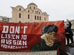 An activist outside the Dutch embassy in Kiev, Ukraine, holds a banner that says not to listen to Russian propaganda, February 5, 2016, photo by Gleb Garanich/Reuters