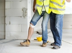 Construction worker helping an injured worker walk