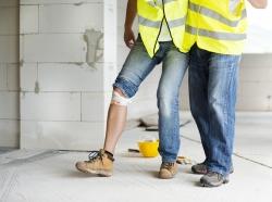 Construction worker helping an injured worker walk