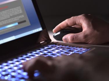 Man using a laptop in a dark room