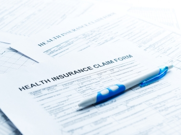 Pen on top of health insurance claim forms, photo by Valeriya/Getty Images