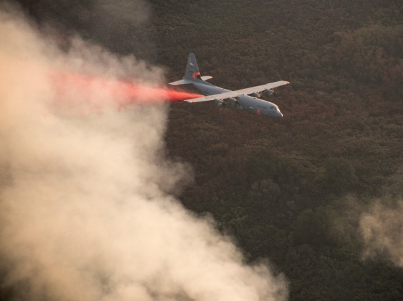 A C-130J Hercules from the 146th Airlift Wing, California Air National Guard, sprays fire retardant ahead of the leading edge of the Thomas Fire, Dec. 13, 2017, photo by Master Sgt. Brian Ferguson/U.S. Air Force