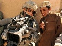 Master Sgt. Robert Carreon shows an Afghan student his footage Jan. 7, 2010, at the Bazaar school in Hutal, Afghanistan. Sergeant Carreon is a videographer with 4th Combat Camera and was attached to the 5th Brigade, 2nd Infantry Division.