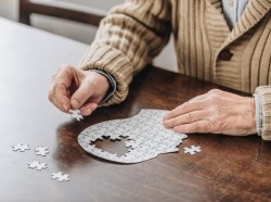 A senior man playing with a puzzle, photo by LightFieldStudios/Getty Images
