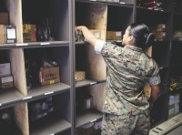 Sgt. Angie Novoa, a warehouse chief with Special Purpose Marine Air-Ground Task Force Crisis Response-Africa, organizes a shelf in her warehouse on Naval Air Station Sigonella, Italy, Oct. 28, 2016