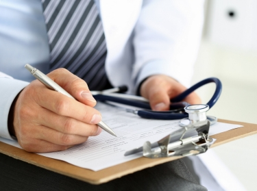 Male doctor filling out medical forms on a clipboard, holding a stethoscope, photo by megaflopp/Getty Images