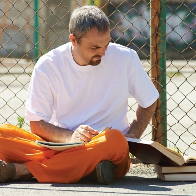 A man studying in prison, photo by mediaphotos/Getty Images