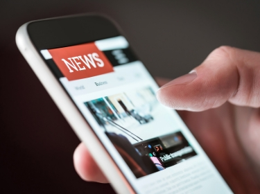 Person scrolling through the news on a smartphone, photo by Adobe Stock/terovesalaine