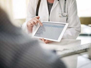Doctor showing a patient information on a digital tablet, photo by Cecilie_Arcurs/Getty Images