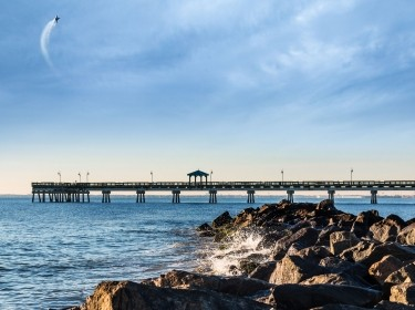 Fighter jet flying over a jetty at Buckroe Beach in Hampton, Virginia, photo by sherryvsmith/Adobe Stock and ozgurdonmaz/Getty Images
