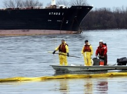 Emergency workers float along an oil collection boom in front of Athos I after it spilled 30,00 gallons of crude oil into the Delaware River in Philadelphia, November 28, 2004, photo by Tim Shaffer/Reuters
